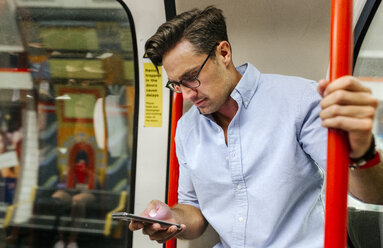 UK, London, businessman in underground train looking at cell phone - MGOF03795