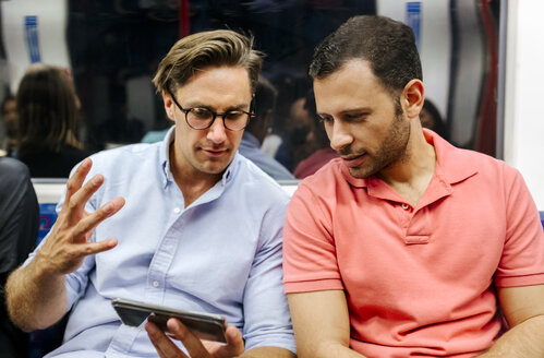 Portrait of two friends sharing cell phone in subway - MGOF03798