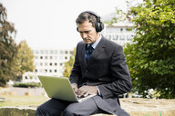 Businessman in city park wearing headphones and using laptop - MOEF01379
