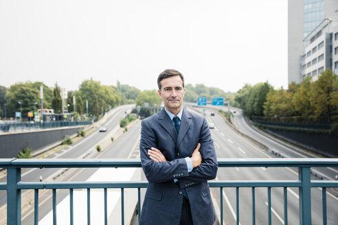 Portrait of confident businessman standing on motorway bridge - MOEF01388