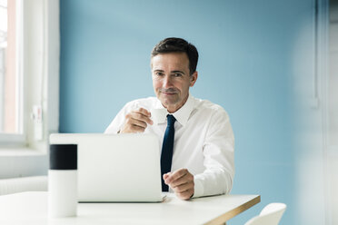 Portrait of confident businessman using laptop on table in office - MOEF01391