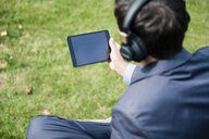 Businessman wearing headphones and using tablet outdoors - MOEF01397
