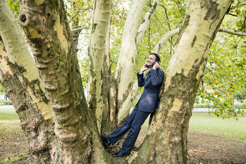 Smiling businessman wearing headphones at a tree - MOEF01406