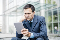 Serious businessman using tablet in the city - MOEF01418