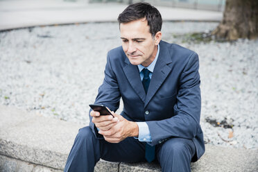 Businessman sitting down using cell phone in the city - MOEF01421