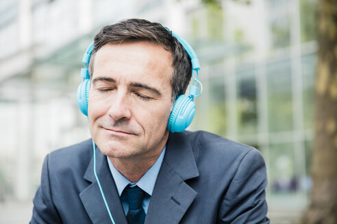 Businessman with closed eyes listening to music with headphones in the city - MOEF01424