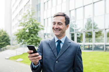 Laughing businessman looking at cell phone in the city - MOEF01427