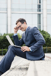 Smiling businessman sitting down using laptop in the city - MOEF01433