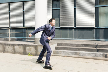 Businessman inline skating in the city - MOEF01436