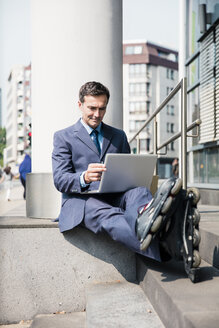Businessman with inlineskates sitting down using laptop in the city - MOEF01439