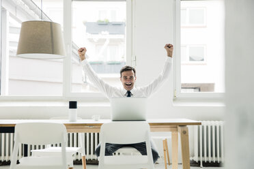 Laughing businessman with laptop on table cheering in office - MOEF01448