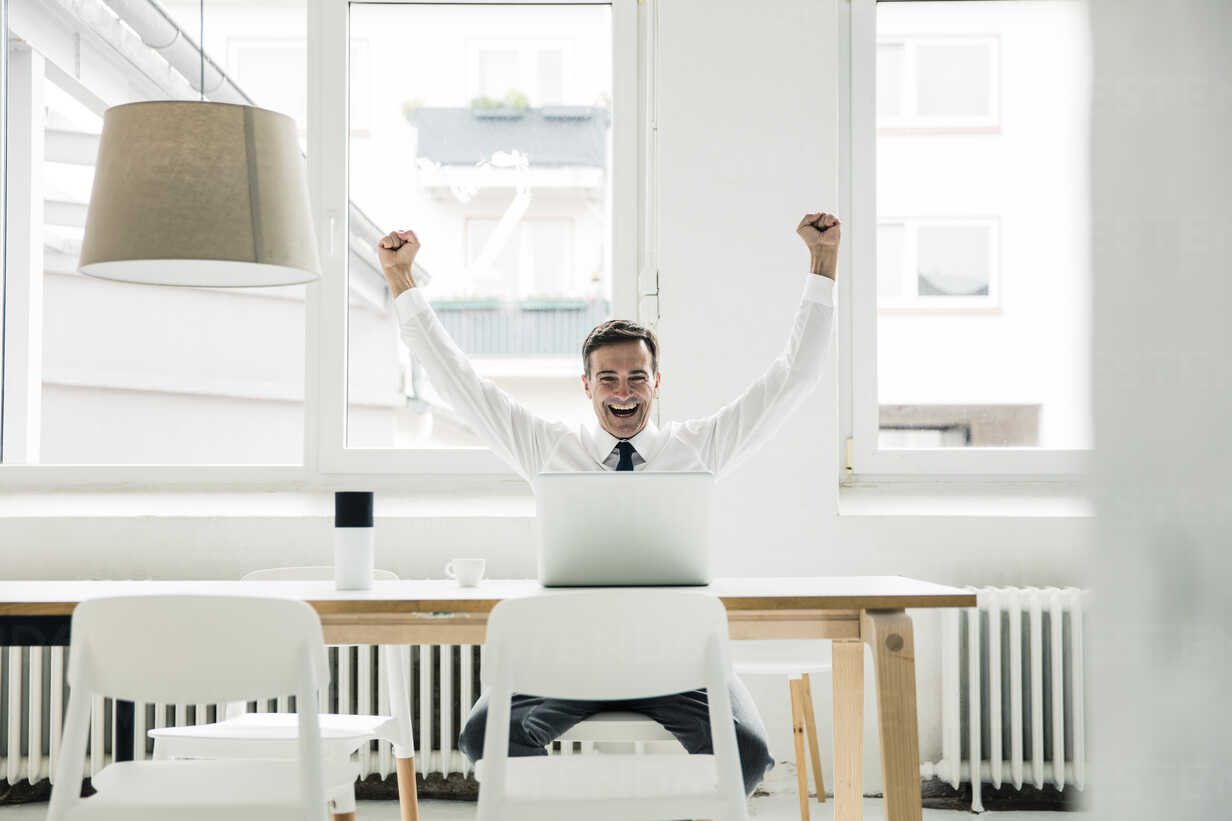 Laughing businessman with laptop on table cheering in office - MOEF01448 - Robijn Page/Westend61