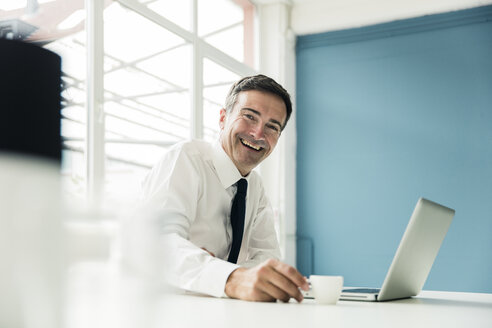 Portrait of laughing businessman with laptop on table in office - MOEF01451