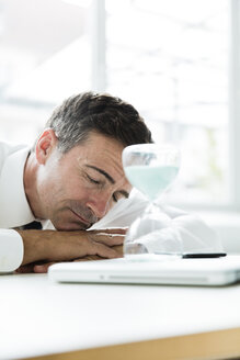 Businessman sleeping on table in office with hourglass - MOEF01454