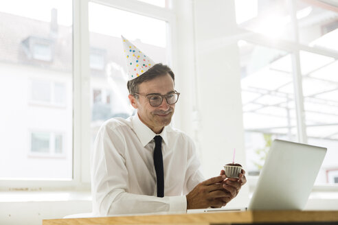 Businessman with laptop celebrating birthday in office - MOEF01460