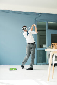 Businessman wearing VR glasses playing golf in office - MOEF01463