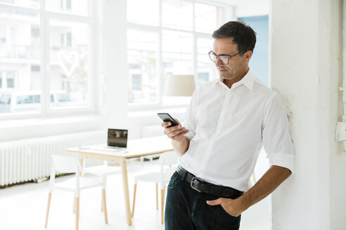 Businessman looking on cell phone in bright office - MOEF01466