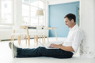 Smiling businessman sitting on the floor in office using laptop - MOEF01478