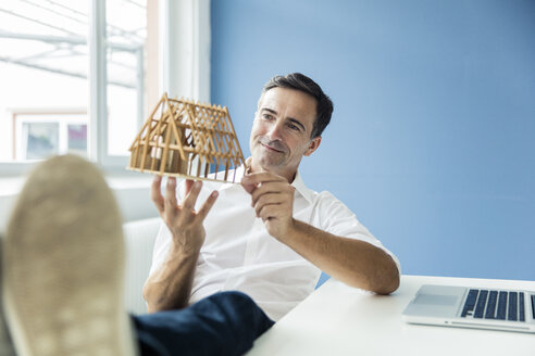 Confident businessman looking at model house in office - MOEF01481