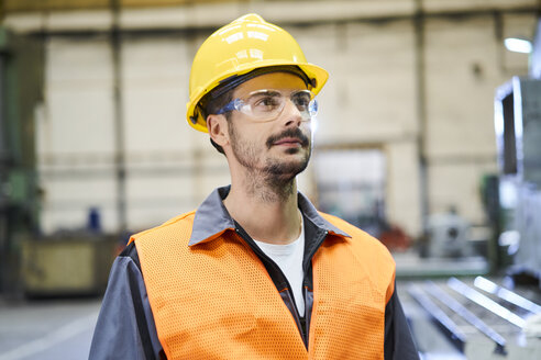 Man wearing protective workwear looking around in factory - BSZF00587