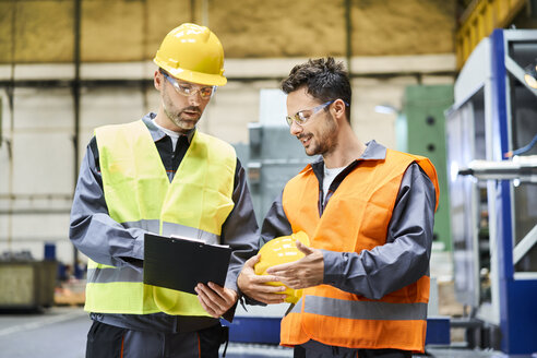Two men wearing protective workwear holding clipboard and talking in factory - BSZF00590