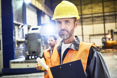 Portrait of confident man wearing protective workwear in factory - BSZF00593