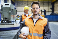 Portrait of serious man wearing protective workwear in factory - BSZF00596