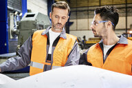 Two men wearing protective workwear discussing plan in factory - BSZF00599