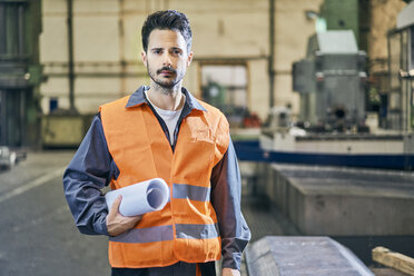Portrait of serious man holding blueprints in factory - BSZF00608