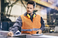 Man wearing protective workwear working in factory - BSZF00611