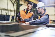 Two men wearing protective workwear working with tablet in factory - BSZF00614