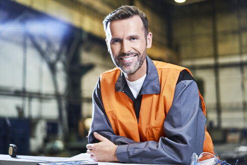 Portrait of smiling man in factory wearing safety vest - BSZF00617