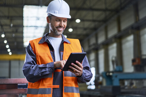 Smiling man using tablet in factory - BSZF00623