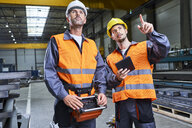 Two men in factory talking and operating machinery with remote console - BSZF00626