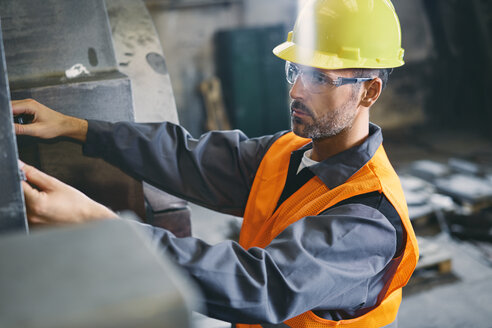 Man wearing protective workwear working in factory - BSZF00629