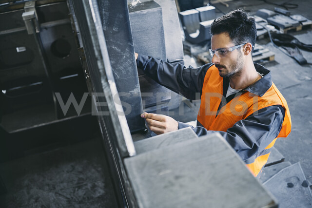 Man wearing protective workwear working in factory - BSZF00632