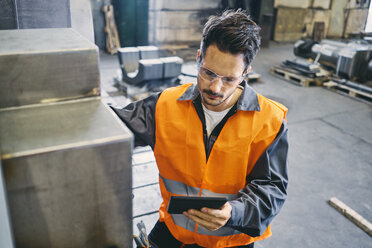 Man with tablet wearing protective workwear working in factory - BSZF00635