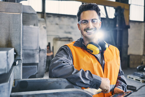 Portrait of smiling man wearing protective workwear and holding tablet in factory - BSZF00638