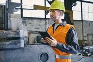 Man with tablet wearing protective workwear working in factory - BSZF00641