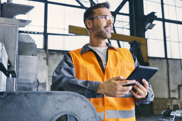 Smiling man with tablet wearing protective workwear in factory - BSZF00644