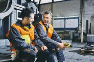 Two men wearing protective workwear talking during break in factory - BSZF00647