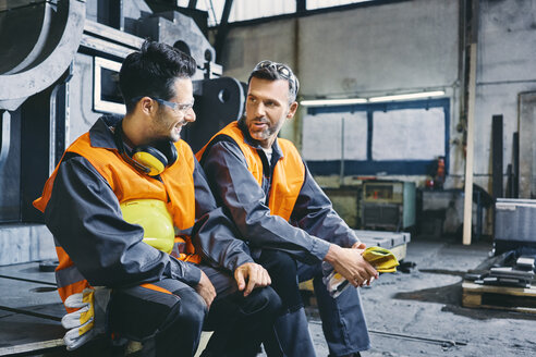 Two men wearing protective workwear talking during break in factory - BSZF00647