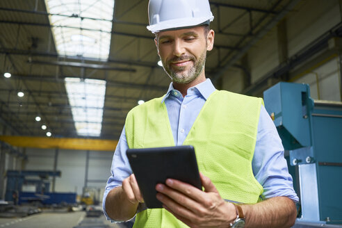 Confident man wearing shirt and safety vest using tablet in factory - BSZF00659