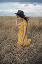 Young woman wearing summer dress with floral design and a hat standing in corn field - VPIF00870