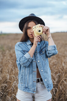 Portrait of young woman wearing hat and denim jacket taking photo of viewer - VPIF00888
