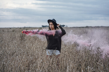 Portrait of young woman standing in a corn field with smoke torch - VPIF00897