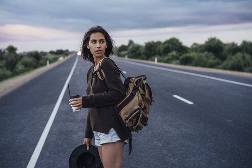 Portrait of young hitchhiking woman with backpack and beverage standing on lane - VPIF00903