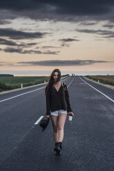 Portrait of hitchhiking young woman with backpack and beverage walking on lane at evening twilight - VPIF00906