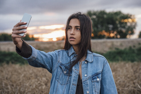Portrait of young woman taking selfie with smartphone in nature at sunset - VPIF00909