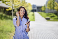 Portrait of student using smartphone and earphones on campus - JSMF00471